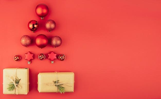 빨간색 배경에 빨간색 크리스마스 볼 선물 상자로 만든 크리스마스 트리입니다. 플랫 lay.banner.copy 공간