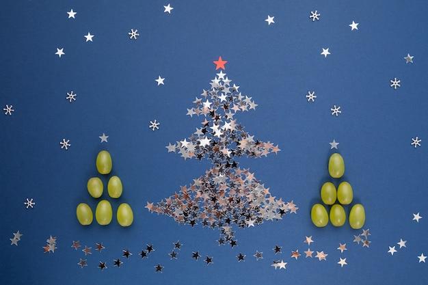 Елка из пайеток в виде звездочек и винограда. в испании принято есть 12 ягод на удачу в полночь. новогодняя композиция.
