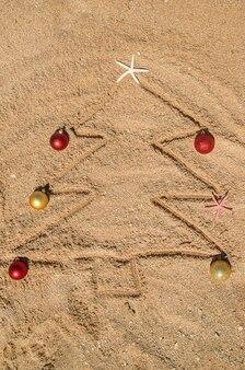 모래에 조개 껍질로 만든 크리스마스 트리. 선택적 초점입니다. 자연.
