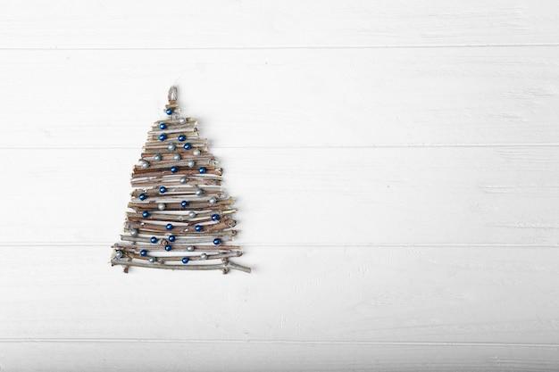 木製の背景に棒とビーズで作られたクリスマスツリー