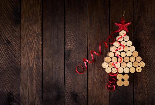Рождественская елка из винных пробок на деревянных фоне. макет открытки с елкой и копией пространства для текста. вид сверху.