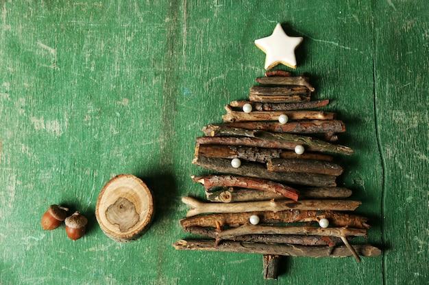 Рождественская елка из деревянных веток на деревянном столе, вид сверху
