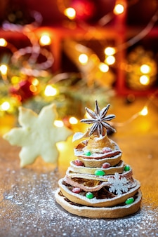 Christmas tree made out of dried orange slices and anise star, with festive light and cookie
