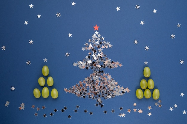 Christmas tree made of sequins in the shape of stars and grapes. spanish traditional to eat 12 berries for good luck at midnight. new year composition.