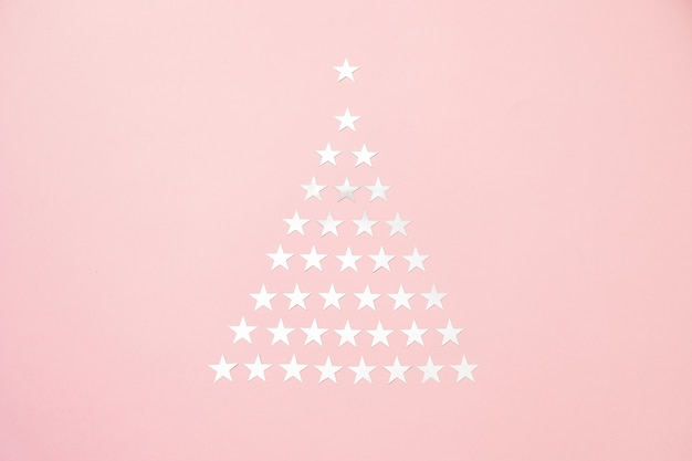 Christmas tree made of silver star sprinkles confetti. flat lay. holiday concept