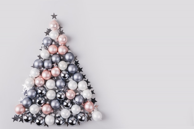 Christmas tree made of stars, silver balls on grey background. xmas composition. flat lay, top view, copy space. holiday greeting card.
