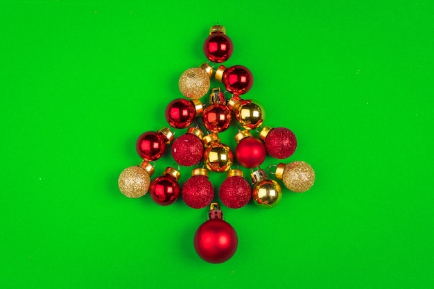 Christmas tree made with small baubles on green background