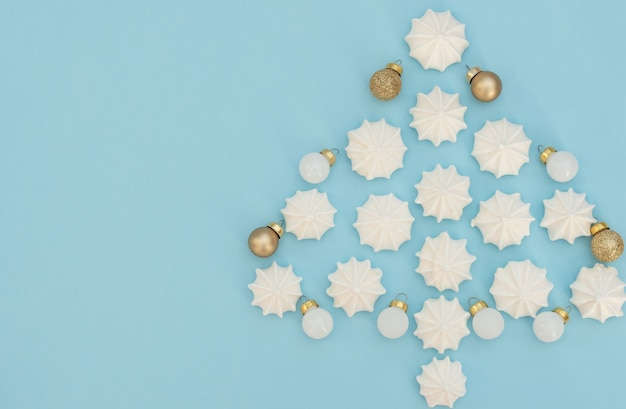金色と白のクリスマスの装飾が施された白いメレンゲで作られたクリスマスツリー