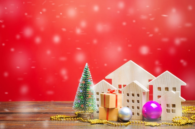 Christmas tree, miniature wooden houses and gifts. new year or xmas winter holiday.