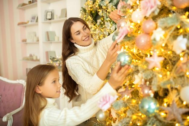 Рождественская елка. мама и дочь вместе украшают елку и выглядят довольными