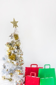Christmas tree near shopping bags
