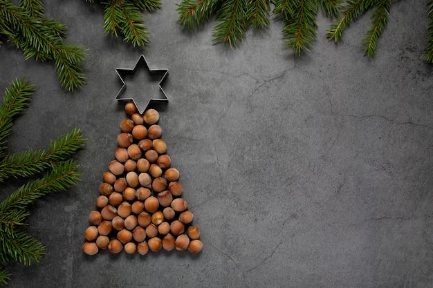 上にクッキーカッターと木の枝とヘーゼルナッツのクリスマスツリー