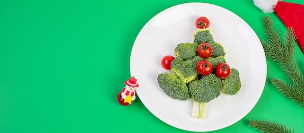 Рождественская елка из органических овощей на белой тарелке