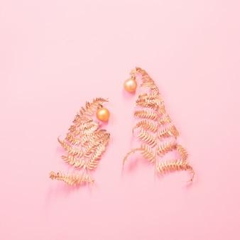 Рождественская елка из расписных золотых листьев папоротника на розовом бумажном фоне
