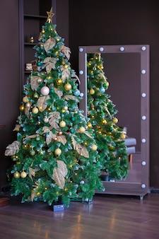Новогодняя елка на коричневом фоне в интерьерной фотостудии.