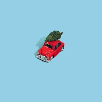 青い背景の上の赤いおもちゃの車の上のクリスマスツリー