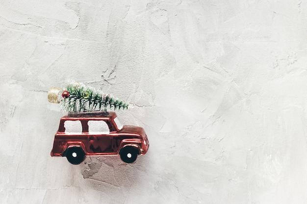 レトロな赤い車のおもちゃの装飾のクリスマスツリー。お祝いの抽象的な冬の休日の背景。クリスマスと新年のショッピング、お祝い、パーティーのコンセプト