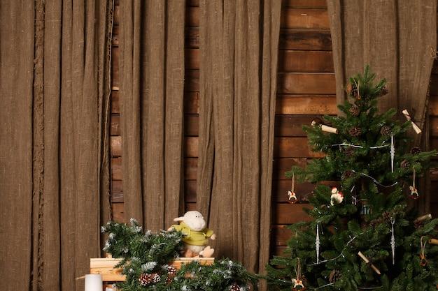 Рождественская елка на коричневой мешковине и деревянной стене