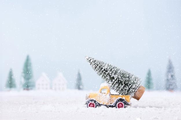 장난감 자동차에 크리스마스 트리는 자연 풍경 배경의 분야에서 눈을 통해 실행되었습니다.
