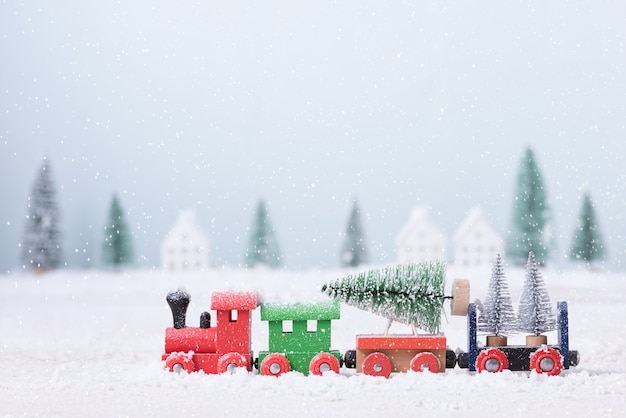장난감 기차에 크리스마스 트리는 자연 풍경 배경의 분야에서 눈을 통해 실행되었습니다.