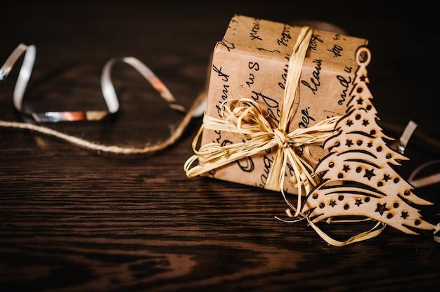 Елочные украшения и подарок, коробка с лентами на коричневом структурном деревянном столе. вид сбоку, место для текста.