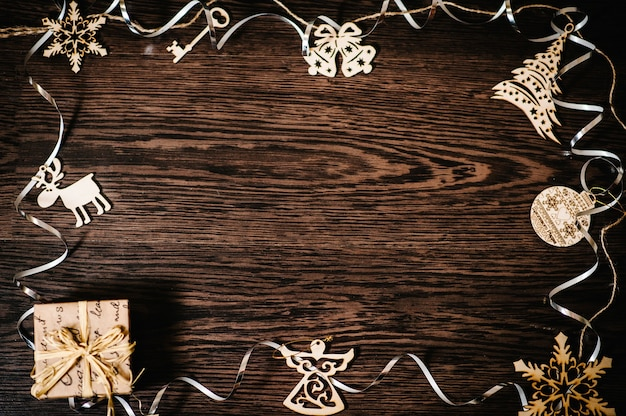 クリスマスツリーの装飾品、ギフト、リボン付きボックス、雪片、鐘、鹿、茶色の構造的な木の背景に天使。フラットレイ。上面図、テキスト用のスペースのあるフレーム。幸せな休日。