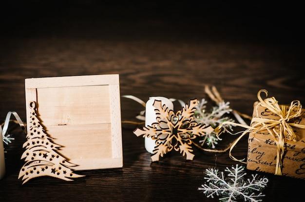 クリスマスツリーの飾り、ギフト、リボン付きボックス、雪片、茶色の構造的な木の背景にキャンドル。側面図、テキスト用のスペースのあるフレーム。幸せな休日。メリークリスマス、新年のコンセプト。