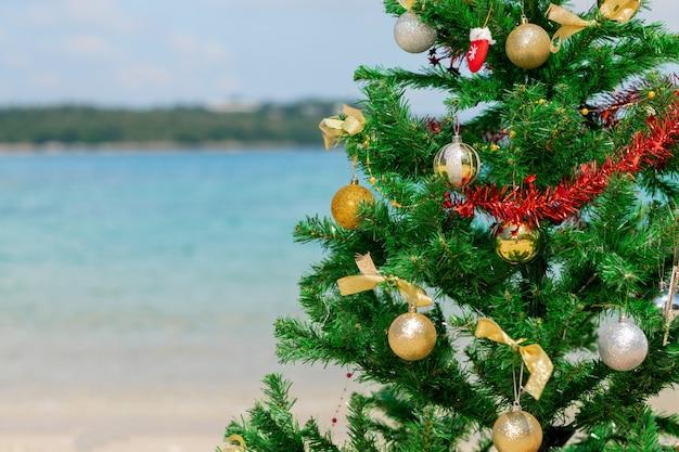 ビーチの背景の上のクリスマスツリー。休暇の目的地。