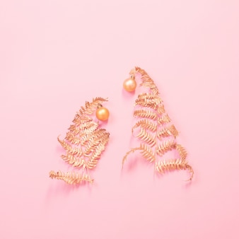 Christmas tree of painted golden leaves fern on pink paper background