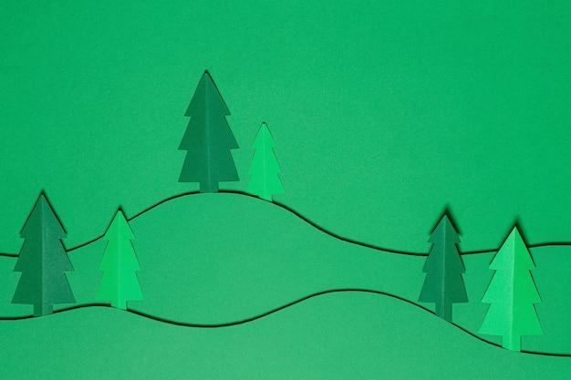 Карточка papercraft дизайна резки бумаги рождественской елки. вырезанные из бумаги елки. креативный дизайн рождественского фона с бумажной елью. художественная картина с лесом, рождественской елью. поделки из бумаги.
