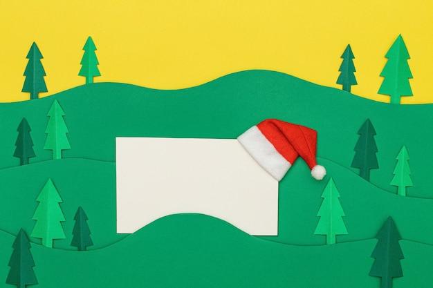 Карточка papercraft дизайна вырезывания бумаги рождественской елки с шляпой санта-клауса. вырезанные из бумаги елки. креативный дизайн рождественского фона с бумажной елью. поделки из бумаги.