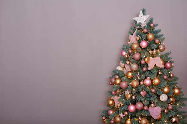 Christmas tree in pink loft style interior.  christmas tree on gray background