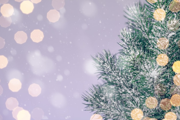 Christmas tree on a purple background with golden lights, copy space