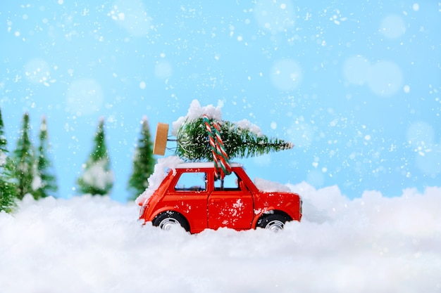 Christmas tree on red car toy with blurred tree and snow. christmas holiday celebration card