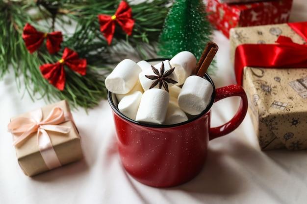 マシュマロギフトアニスとシナモンスティックとクリスマスツリーの赤いカップお祝いのクリスマスカード