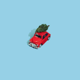 Christmas tree on a red toy car on blue background