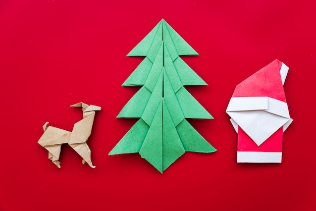 Christmas tree; reindeer; santa claus paper origami on red backdrop