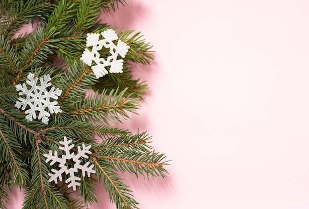 Christmas tree's branch with three white snowflakes on pink background with copy space