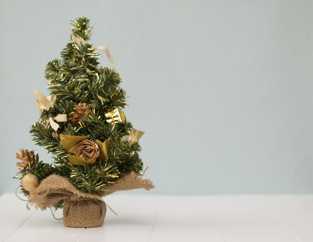 Christmas tree in the sacking on a wooden table.