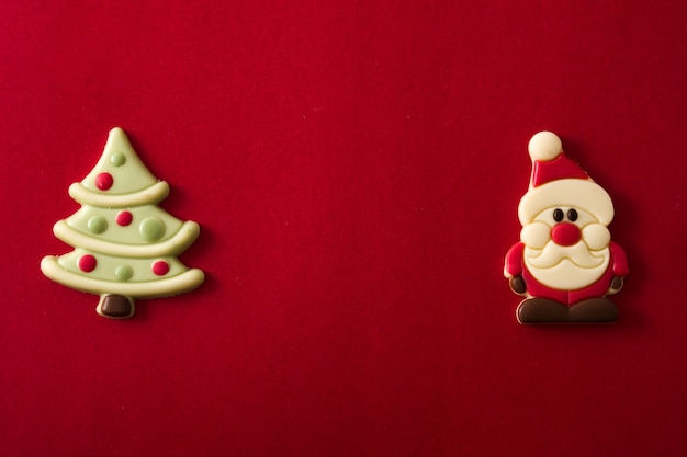 Christmas tree and santa claus chocolate bonbons on red background