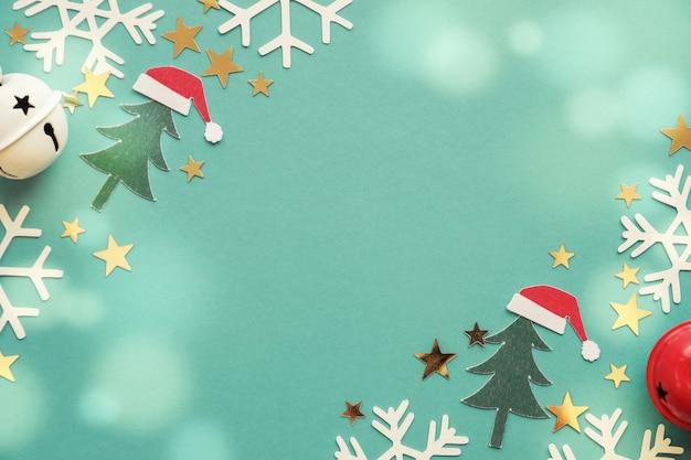 緑のパステル調の背景にクリスマスツリー、サンタ帽子、雪片の装飾