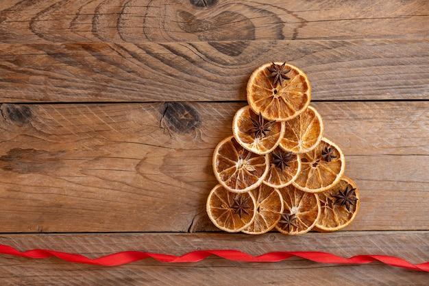 나무 배경에 말린 오렌지로 만든 크리스마스 트리 모양, 위쪽 전망. 지속 가능한 크리스마스. 전통적인 크리스마스 재료 - 오렌지, 계피, 스타 아니스. 빈티지 크리스마스 장식입니다.