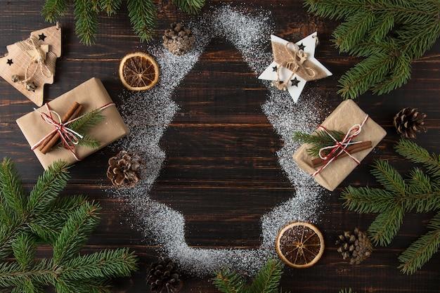 Новогодняя елка, подарки, еловые ветки и украшения на деревянном столе. вид сверху.