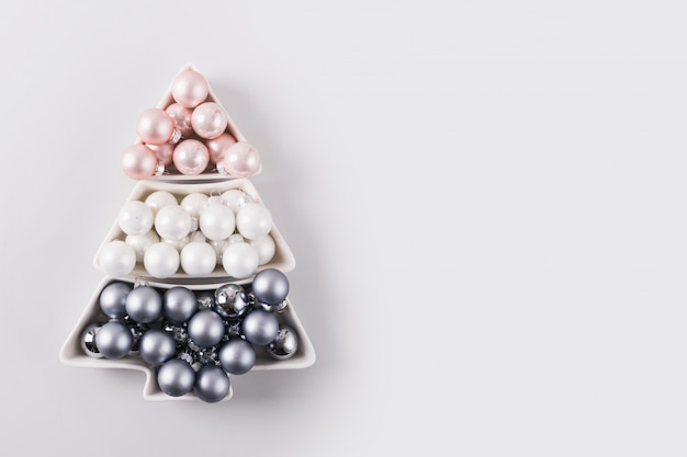 Christmas tree of silver balls on grey background. xmas composition. flat lay, top view, copy space. holiday greeting card.