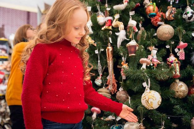 クリスマスツリー。家庭用店で家の装飾やホリデーギフトを探している家族、母親、子供たちの笑顔。挨拶やデザインのためのスタイリッシュなレトロなもの。時間を祝うインテリアリノベーション。