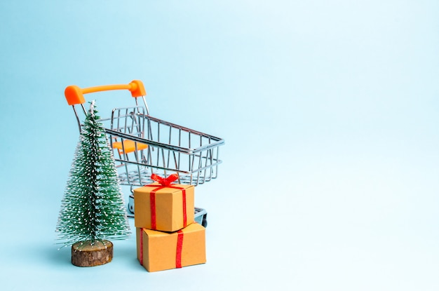 Christmas tree, supermarket cart and gift on a blue background.