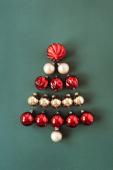 Christmas tree symbol made of red and gold christmas baubles balls on green