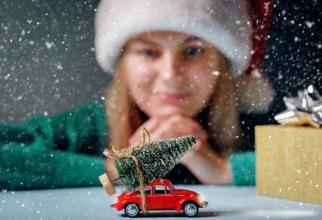 A christmas tree tied to a toy car on a table, a girl dressed in a santa hat is dreamily looking at a typewriter.