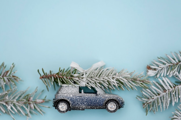 Christmas tree on a toy car on a blue backgroundchristmas holiday and new year background concept