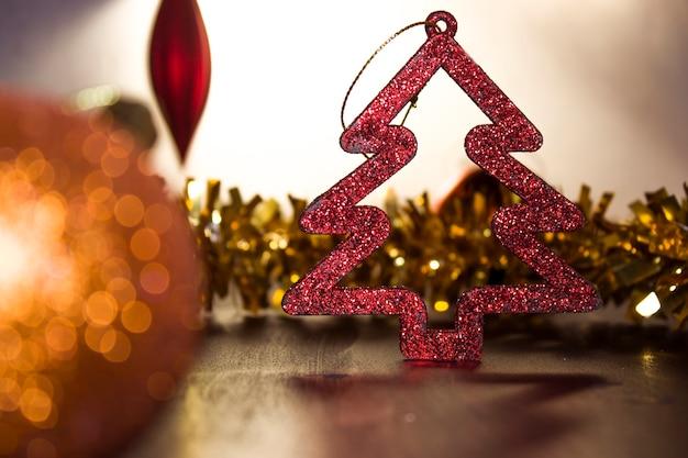 クリスマスツリーのおもちゃ、クリスマスの金とオレンジのボール、バックライト、輝き。クリスマスデザインの背景